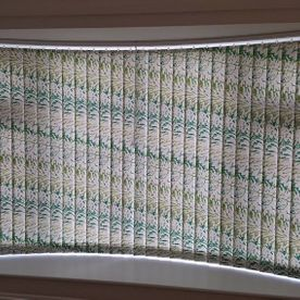 vertical blinds in a curved bay window with a diagonal pattern running through